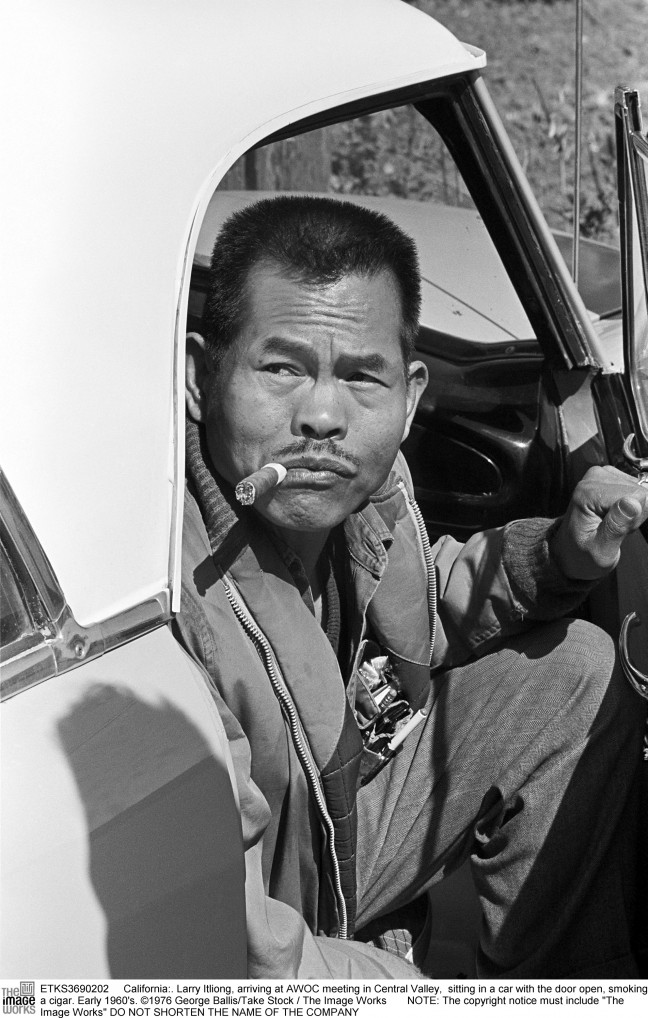 California: ca. 1965. Larry Itliong sitting in a car with the door open, smoking a cigar. ©1976 George Ballis/Take Stock / The Image Works