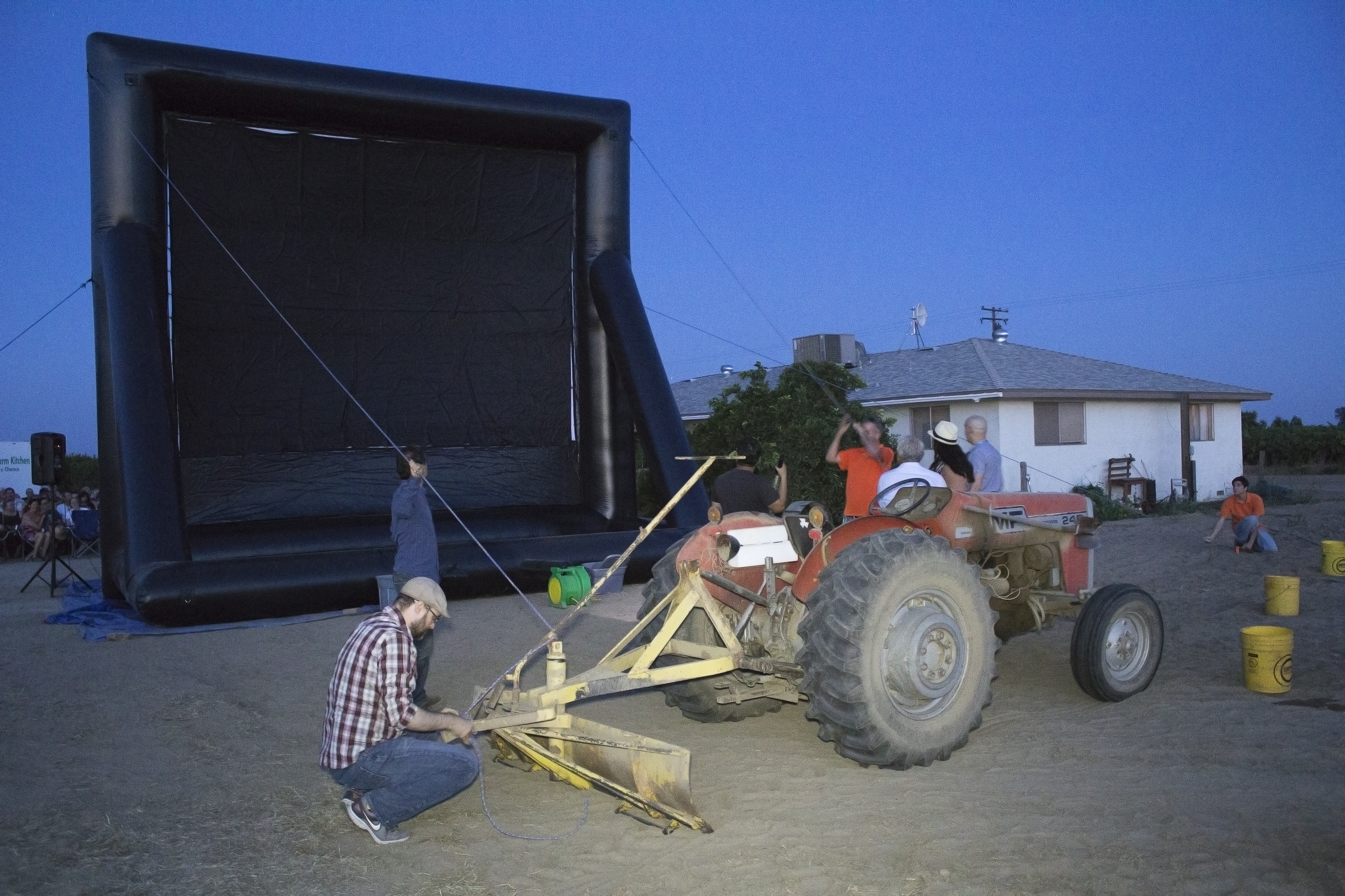 Mas comes to the rescue and fires up his tractor, tethering the screen to the tractor and re-inflating it. Photo by Diana Li
