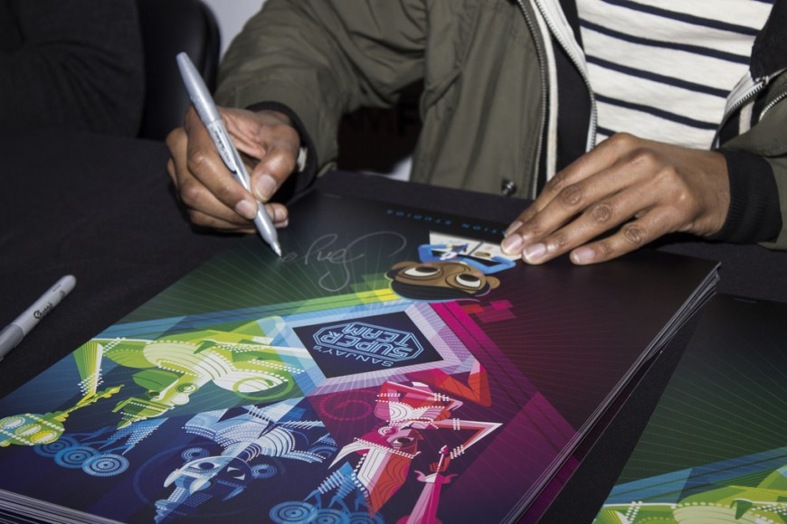 """Sanjay Patel, creator of """"Sanjay's Super Team,"""" signs a poster at the panel. Photo by Subhrajit Bhatta"""