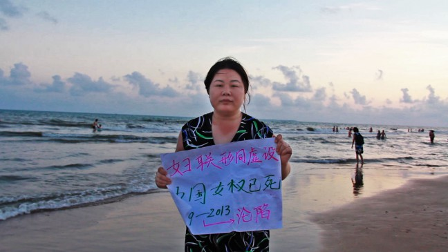 "In May 2013, Ye Haiyan, AKA Hooligan Sparrow held up a sign at a protest against an elementary school principal and a government official who raped six girls aged between 11 and 14 in Wanning City, Hainan Province. The sign reads: ""All China Women's Federation is a farce. China's women's rights are dead. 1949-2013 Fallen."" Credit: Nanfu Wang"