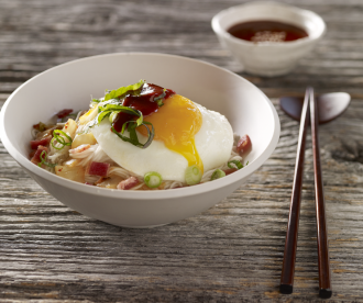 Spicy noodles with fried egg, bacon & kimchi topped with perilla leaves by @futondesk